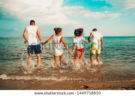 Group of young multiethnic friends women and men at the beach in summertime back jumping