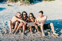 group of young multiethnic friends women and men at the beach in summertime using tablet handhold, looking and touching the screen - technology, internet, social network concept