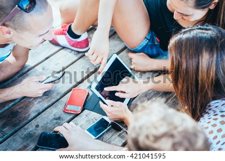 group of young multiethnic friends women and men at the beach in summertime using technological devices smart phone and tablet - social network, technology, communication concept #421041595