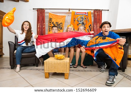 Group of young multiethnic soccer fans cheering while watching match at home