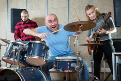 Group of young musicians with expressive male drummer practicing in rehearsal room