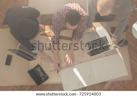Group of young people / architects being creative in a small office. #725914003