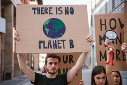 Group of young people at a demonstration for the environment - Young millennials protest at a procession to save the planet with slogans and drawn in the sign - Concept of manifestation