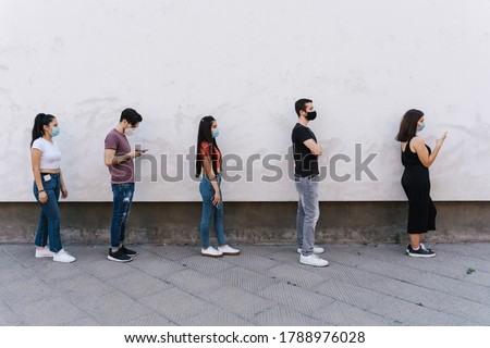 Group of young people at safety distance near a white wall in queue in protection by Coronavirus, Covid-19 with face mask while using the device - Multiracial group of friends - Concept of security Photo stock ©