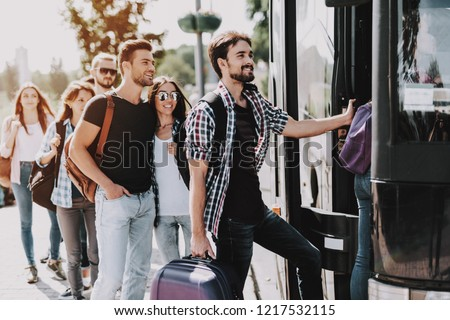 Group of Young People Boarding on Travel Bus. Happy Travelers Standing in Queue Holding Luggage Waiting their turn to Enter Bus. Traveling, Tourism and People Concept. Summer Vacation