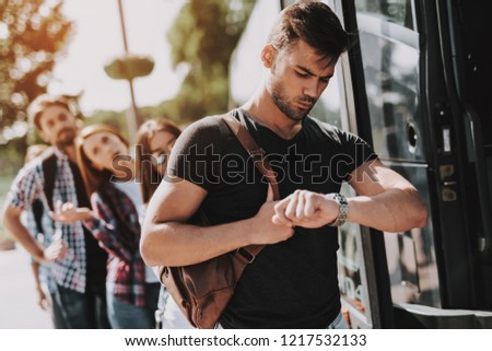 Group of Young People Boarding on Travel Bus. Unhappy Travelers Standing in Queue Holding Luggage Waiting their turn to Enter Bus. Traveling, Tourism and People Concept. Summer Vacation