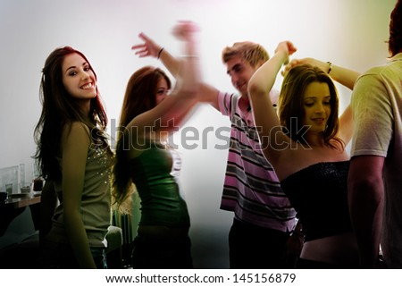Group of young people dancing in a night club with their arms up to the rhythm of the music with color lights, having fun and being happy, indoors.