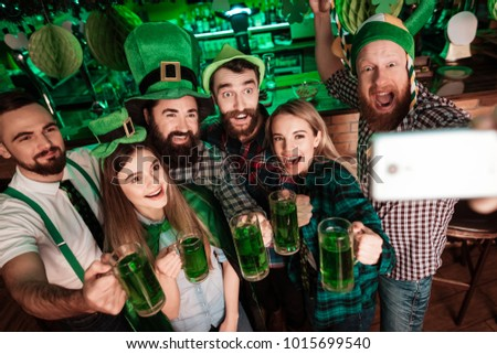 Group of young people doing selfie on a mobile phone in a bar. They celebrate St. Patrick's Day. They keep glasses with beer.