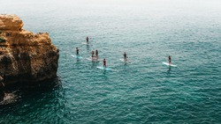 Group of young people doing SUP, Stand up Paddle, in the Algarve.