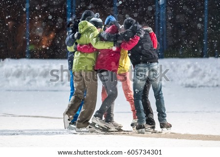 Group of young people embrace on a skating rink #605734301
