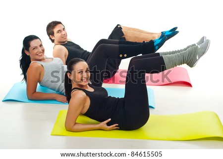 Group of young people exercising on colorful gymnastics mats in a fitness club over white background