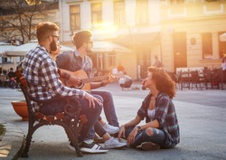 Group of young people hangout at the city street.They sitting on bench ,singing and playing guitar.Sunset.