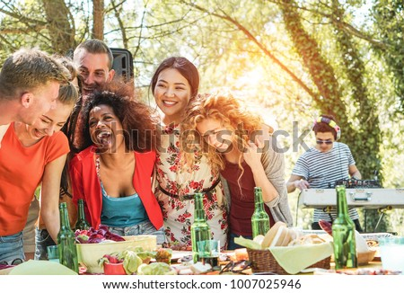 Group of young people having barbecue party music festival in nature - Happy friends laughing and drinking beers in escusive event with dj set mixing outdoor - Focus on afro and asian girls faces  #1007025946