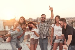 Group of young people having fun at a summertime rooftop party, at sunset. Focus on the people in the middle