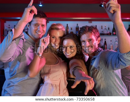Group Of Young People Having Fun In Busy Bar