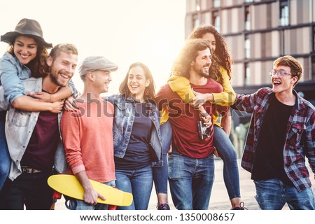 Group of young people having fun in the city center - Happy friends piggybacking while laughing and walking together outdoor - Friendship, millennial generation, teenager and youth lifestyle concept