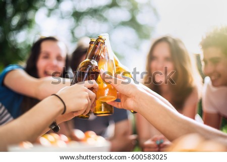 Group of young people having fun sitting around a table outside. Clinking their bottles of beer, focus on the bottles. Shot with flare