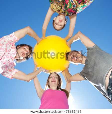 Group of young people hold big yellow ball across blue sky