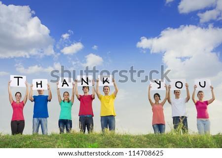 Group of young people holding papers with the words thank you