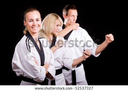 Group of young people in kimono in martial arts training and exercising taekwondo in gym over black background.
