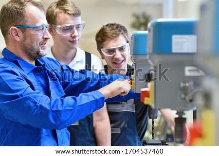 Group of young people in mechanical vocational training with teacher at drilling machine  Stock photo ©