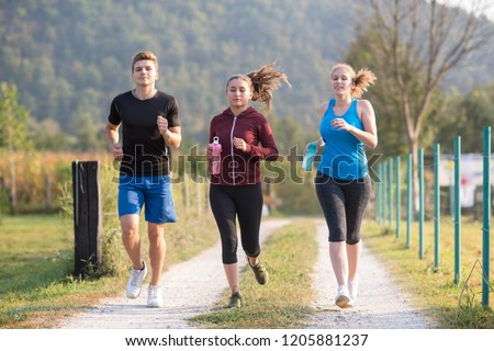 group of young people jogging on country road runners running on open road on a summer day #1205881237