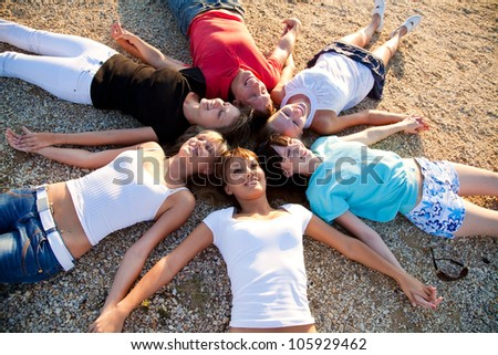 group of young people lie on the beach holding hands enjoying relax