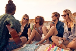 Group of young people listening to friend playing guitar outdoors. Diverse group of friends hanging out at beach. Young men and women drinking beers and enjoying music.