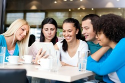 Group of young people looking at tablet in cafe