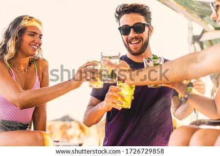 Group of young people making a beach party toasting with alcoholic drinks on the beach kiosk.