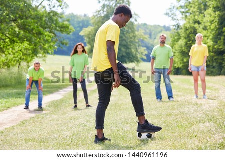 Group of young people on a meadow while playing football as a team event #1440961196