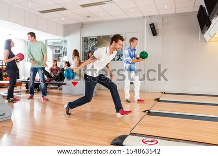 Group of young people playing in bowling alley