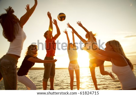 group of young people playing volleyball on the beach