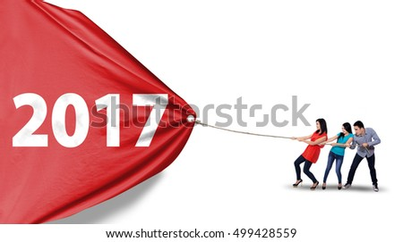 Group of young people pulling a red banner with number 2017 in the studio, isolated on white background