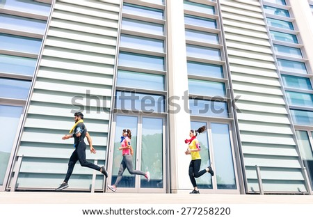 Group of young people running in modern urban area - Fitness girls running with male trainer coach in the city - Sport concept with friends jogging in business center downtown in a sunny bright day