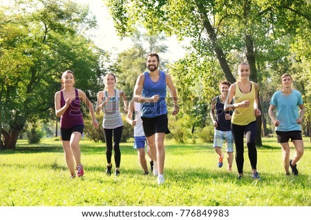 Group of young people running in park #776849983