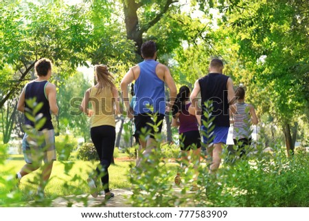 Group of young people running in park #777583909