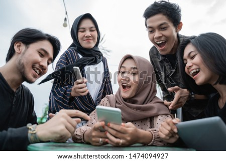 group of young people saw with his friend's handphone