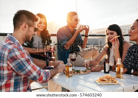 Group of young people sitting around and eating pizza. Friends partying and eating pizza.