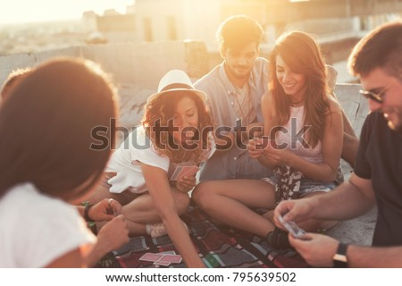 Group of young people sitting on a picnic blanket, having fun while playing cards on the building rooftop. Focus on the couple in the middle #795639502
