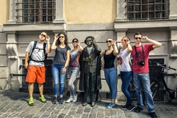 Group of young people standing next to statue of Evert Taube at Järntorget in Stockholm, Sweden