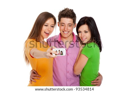 Group of young people taking a self portrait with their phone, happy smiling students friends standing isolated on white background