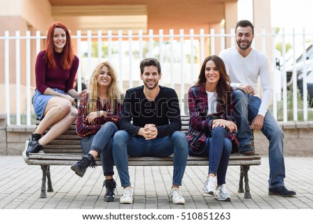 Group of young people together outdoors in urban background. Women and men sitting on a bench in the street wearing casual clothes. #510851263