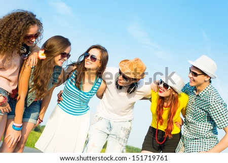 group of young people wearing sunglasses and hats hugging and standing in a row, spending time with friends