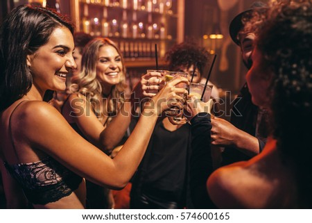 Group of young people with cocktails at nightclub. Best friends partying in a pub and toasting drinks.