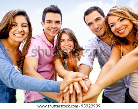 Group of young people with hands together - teamwork concepts