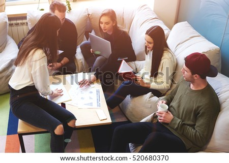 Group of young pupils is preparing for exams while sharing opinions sitting in coworking. Teamwork using computers, books and internet networking.Business professionals accounting income information
