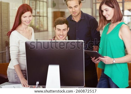 Group of Young Smiling Friends Watching Something at the Computer Screen Together Inside the Office.