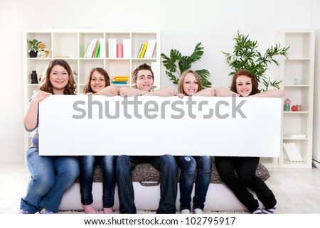 Group of  young smiling teenager holding blank banner in front of them