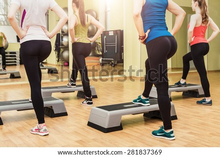 Group of young sportive women making step aerobics in the fitness class - back view